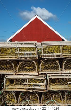 Lobster cage in front of a red barn in Prince Edward Island in Canada
