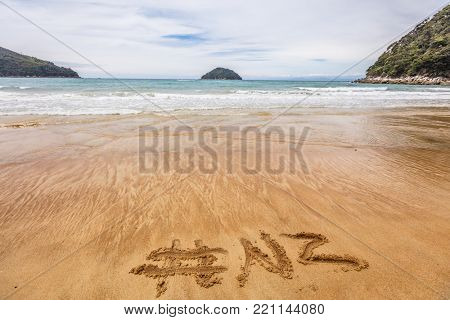 Word NZ hashtag written in sand on New Zealand beach for social media following online advertisement concept. Abel Tasman National Park beach, South Island, New Zealand.