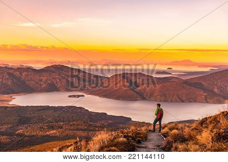 Hiking wanderlust adventure man hiker alone looking at sunset nature landscape of mountains and lakes during summer. Travel outdoors freedom lifestye. poster