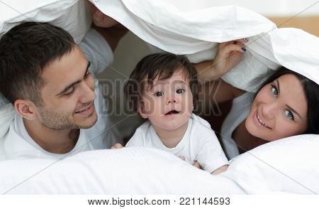 Happy family posing under a duvet while looking at the camera
