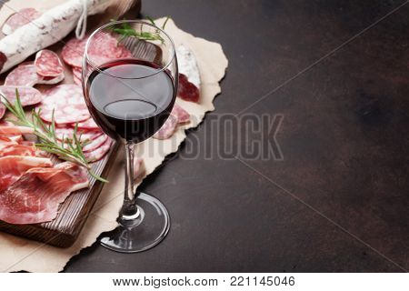 Salami, sliced ham, sausage, prosciutto, bacon and red wine glass. Meat antipasto platter on stone table. With copy space
