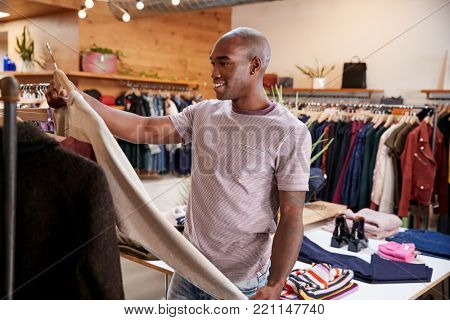 Young black man looking at clothes in clothes shop