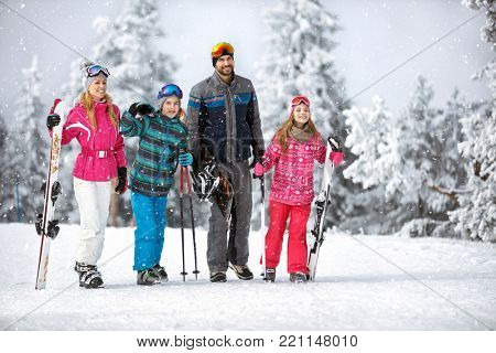 Happy family at winter holiday going to ski terrain with ski equipment