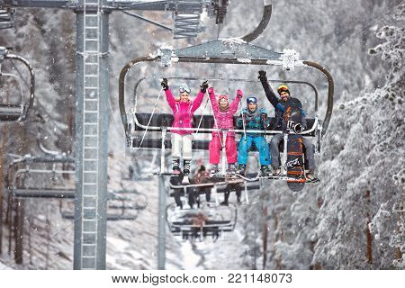 Happy skiers family in ski chair climb up on ski terrain