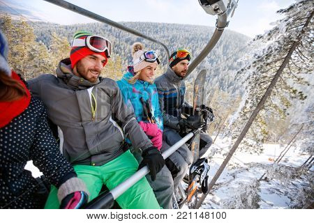 Young male and female skiers lifting on ski terrain with ski lift