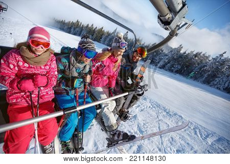 Cheerful parents with children in ski lift lifting on ski terrain