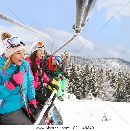 Very happy skiers in ski lift together lifting up on ski terrain