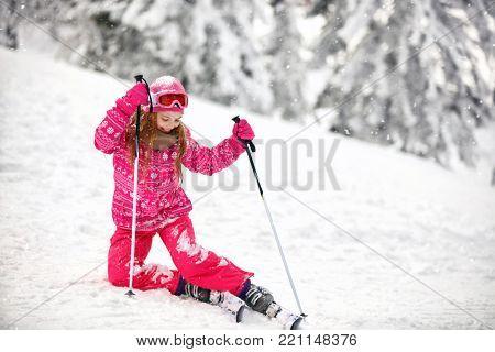Pretty  girl on ski terrain practice to raise from snowy terrain