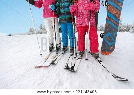 Concept of skis on skiers legs and ski poles on snowy ski terrain