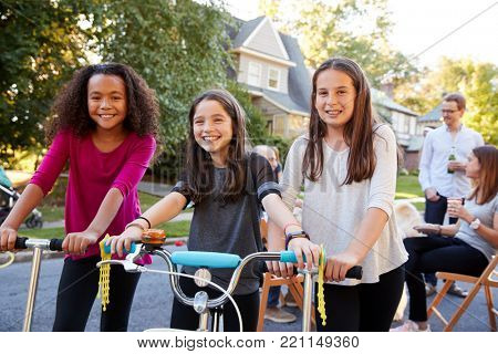 Three pre-teen girls on scooters and a bike at a block party