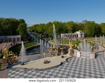 PETERHOF, ST. PETERSBURG, RUSSIA - JUNE 4, 2017: Tourists walking around the Sea canal and the Grand Cascade. The cascade was built in 1715-1724 and is one of the remarkable fountain constructions