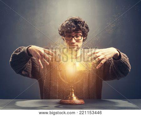 Young man gazing at the glowing crystal ball. Predicting the future. Crystal gazing. Magic.