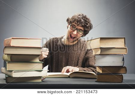 Young man reading a book, studying, looking joyful and excited. Geek concept.