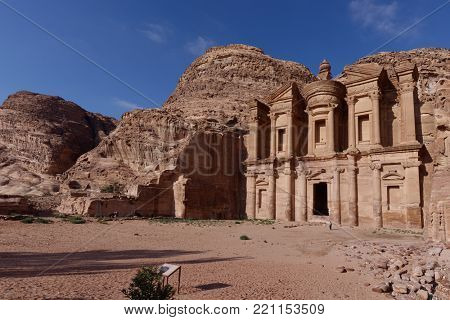 PETRA, JORDAN - MARCH 15, 2014: Tourists near the Monastery, Petra's largest monument. Since 1985, Petra is listed as UNESCO World Heritage site