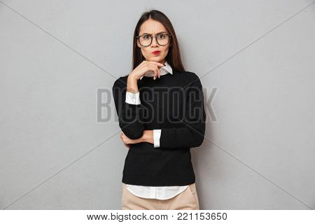 Serious pensive asian woman in business clothes and eyeglasses looking at the camera over gray background