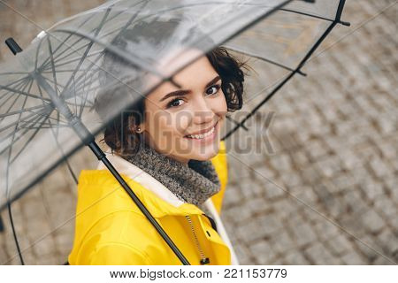 Amazing portrait of young woman in yellow coat, standing under transparent umbrella with broad sincere smile