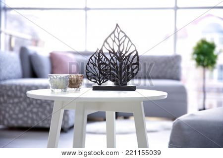 Table with decor and comfortable furniture in living room