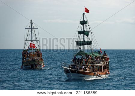ANTALYA, TURKEY - MARCH 26, 2014: Trip boats with tourists approaching to the port. Boat trip is favorite leisure activity for thousands of tourists
