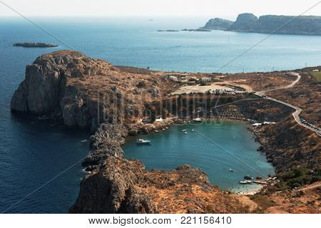 LINDOS, GREECE – OCTOBER 11, 2017: People resting on the beaches of St. Paul's bay. Located 50 km south of the town of Rhodes, Lindos is a popular tourist and holiday destination