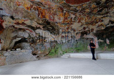 SUMELA MONASTERY, TRABZON, TURKEY - AUGUST 15, 2008: Tourist watching frescoes in the Rock Church of Sumela monastery. Frescoes date back to XVIII century