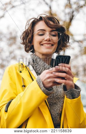 Portrait of beautiful brunette female typing text message or scrolling feed in social network, using her smartphone while being outdoor