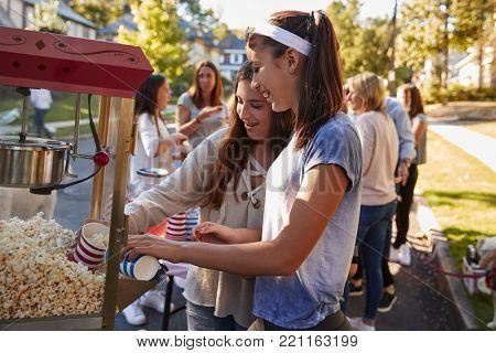 Girls serve themselves popcorn at neighbourhood block party