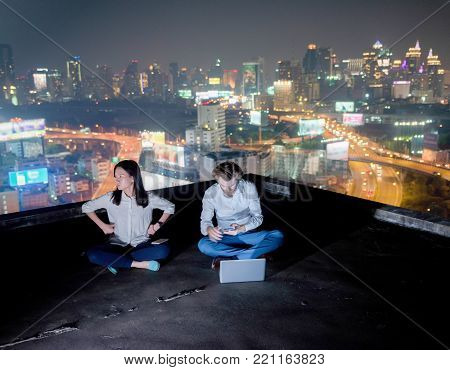 Group of business people working on a rooftop at night with blurry city background, a couple are not interested in each other