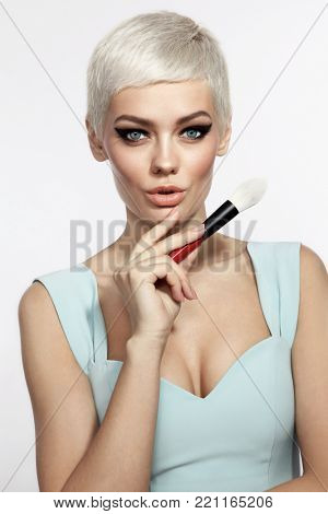 Young beautiful tanned woman with stylish cat eye make-up and platinum blonde hair holding makeup brush  poster