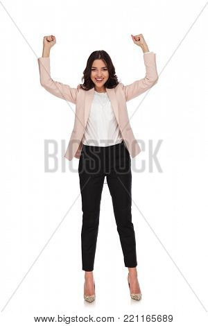 excited young business woman with hands up and fists closed on white background, full body picture