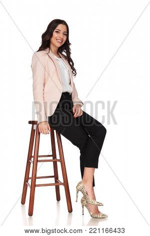 side view of a seated young smiling business woman against white background