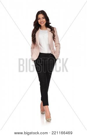 happy relaxed business woman with hands in pockets is walking towards the camera on white background