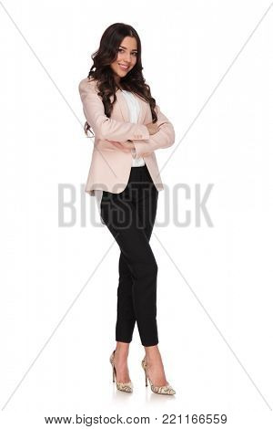full body picture of a beautiful confident business woman with hands crossed standing on white background