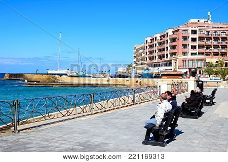 MARSALFORN, GOZO, MALTA - APRIL 3, 2017 - Tourists sitting on benches along the promenade with views towards beach and harbour, Marsalforn, Gozo, Malta, Europe, April 3, 2017.