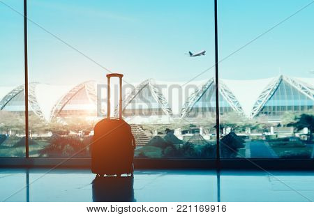 Silhouette suitcase,luggage on side window at airport terminal international and airplane outside on fly flight in the blue sky traveling