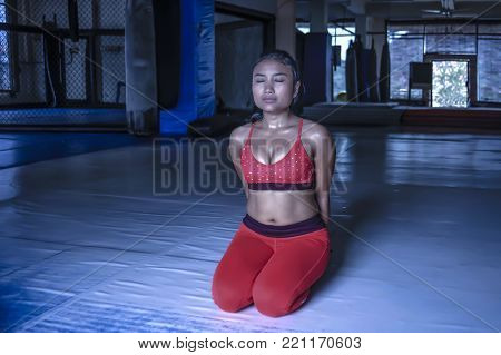 young exhausted sweaty Asian woman in sport clothes breathing and stretching after hard training fitness workout relaxing muscles in intensive exercise session at gym dojo ground floor