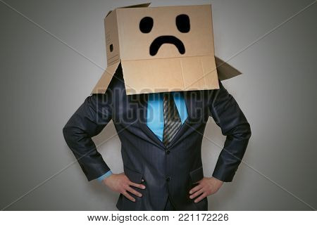 Businessman hides his face inside a cardboard box above his head with drawn sad depressed smile on it.