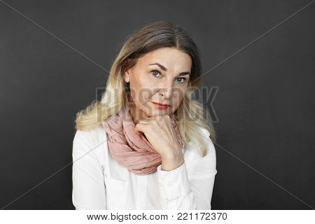 Elegant middle aged lady in stylish clothes holding hand on her chin while thinking over something, being uncertain about making decision, looking at camera with pensive thoughtful expression
