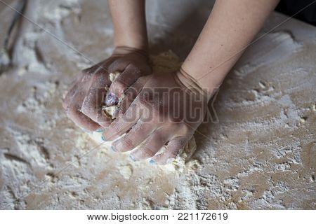 Woman hands kneading dough on table. Flour on the side