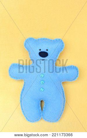 Handmade felt bear - bluу felt bear on yellow background, hand-stitched toy