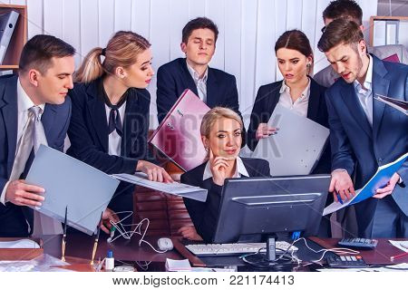 Business people office life of team people working with papers sitting table . Ruthless chief dismisses employees.