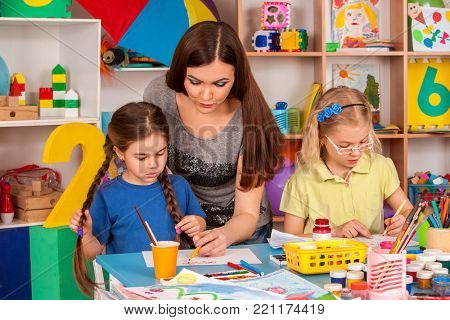 Kids playroom organization of children painting and drawing in kid's club. Craft lesson in primary school. Kindergarten teacher and small students work together. Girl paints felt-tip pen. Children
