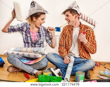 Repair family by happy couple building home. Quarrel family because of renovation in new apartment. Mad woman and man in newspaper cap renovation apartment by painting tools. Newlyweds in new place.