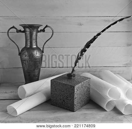 pen in an inkwell with rolls of white paper and an old vase on a table