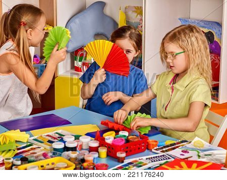 School children with scissors in kids hands cutting paper with teacher in class room. Development and social lerning. Create origami exhibition. Collaboration. Team of students makes paper fans.