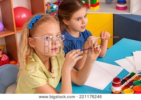 Small students painting in art school class. Child drawing by paints on table. Children listen attentively to teacher in kindergarten. Drawing education develops creative abilities of children.