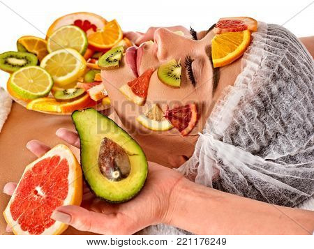 Facial mask from fresh fruits for woman. Beautician apply slices of avocado, grapefruit and kiwi. Treatment of warts with fruit masks. Female enjoys procedure. Top view.
