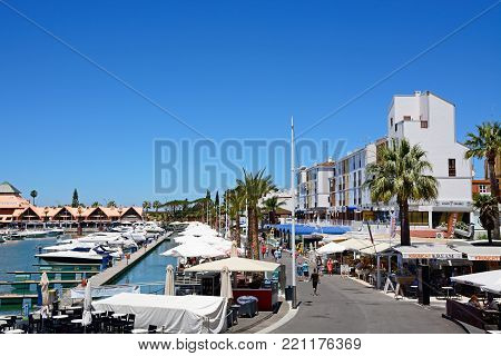 VILAMOURA, PORTUGAL - JUNE 6, 2017 - Boats moored in the marina with tourists walking along the restaurant lined promenade, Vilamoura, Algarve, Portugal, Europe, June 6, 2017.