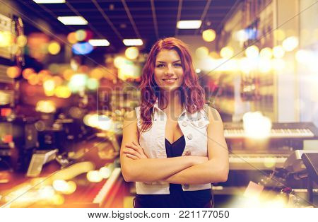 people, musical instruments and small business concept - smiling female assistant or customer at music store over lights