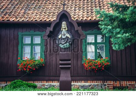 Small chapel in front of traditional wooden house in Piecki village, Masuria region of Poland