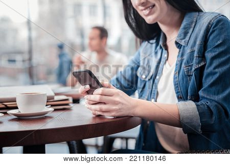 High spirited. Charming female keeping smile on her face and holding telephone while sitting in semi position